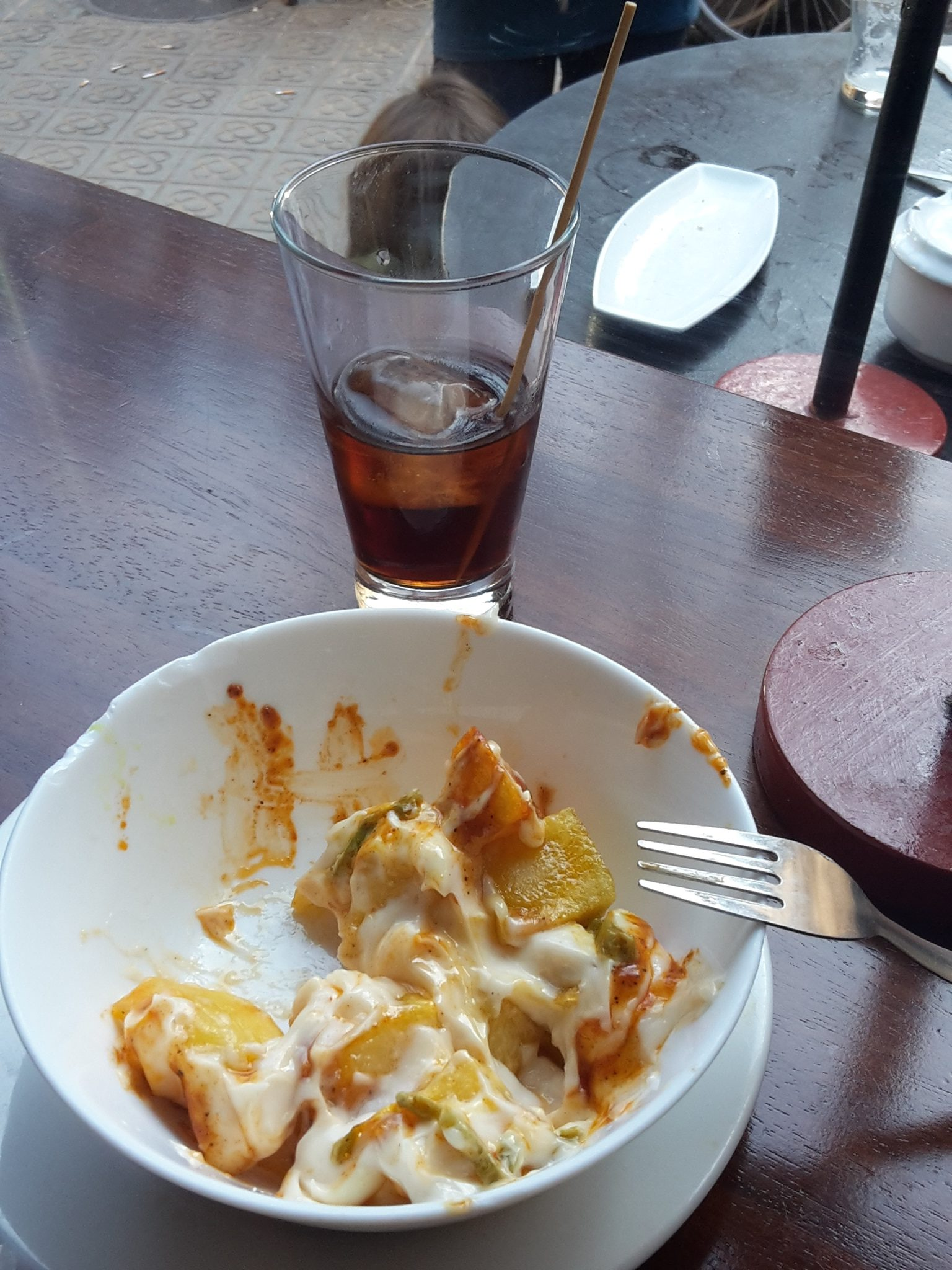 Glass of vermut and half eaten patatas bravas
